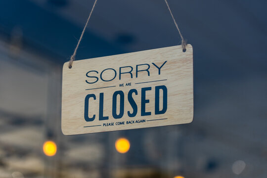 Closed sign broad through the glass of door in cafe., Sorry we're closed sign., Business service and food concept.