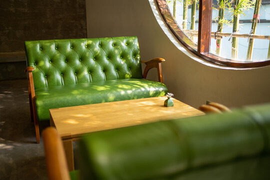 Empty Vintage green leather sofa and table in cafe restaurent, Quiet and chill cafe shop with bamboo view