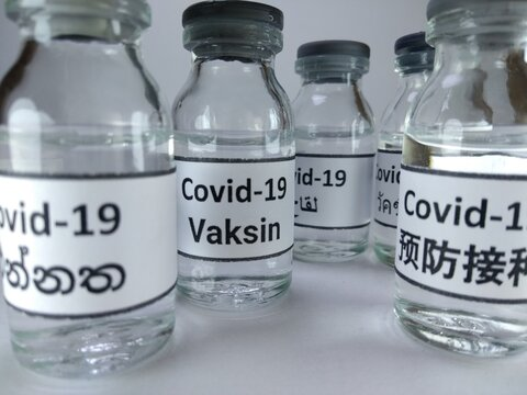 The word Covid 19 vaccine written in different languages ( Chinese, Arabic, Malay, Sinhala) on vaccine bottles
