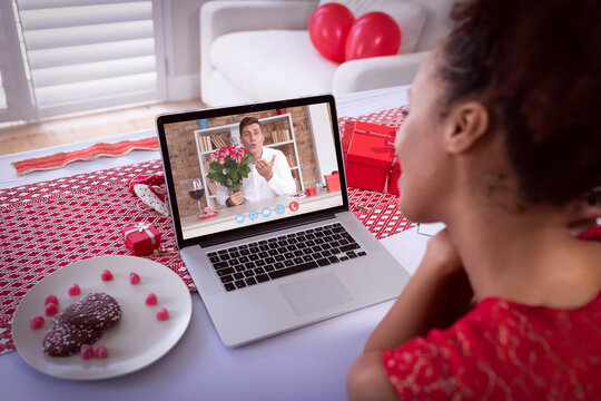 Diverse couple making valentine's date video call the man on laptop screen blowing kiss