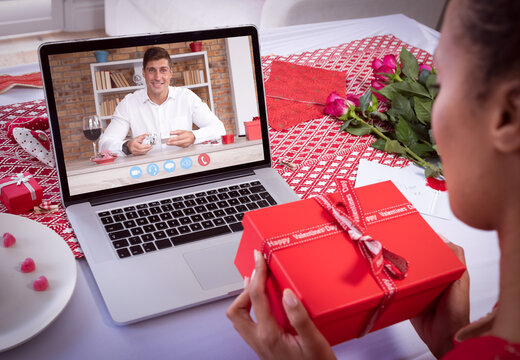 Diverse couple making valentine's date video call using laptop both holding gifts