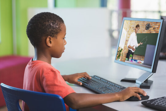 African american schoolboy using computer on video call with male teacher