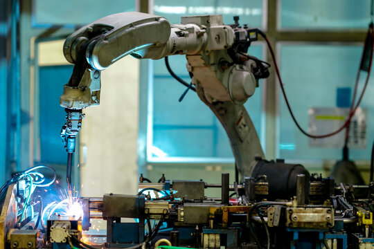 View of robot welding arm in production line of automotive factory.