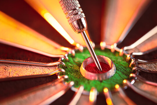 Dartboard showing a dart hit the center bullseye. Concept of success, targeted goal setting and achieving, and aiming for perfection.