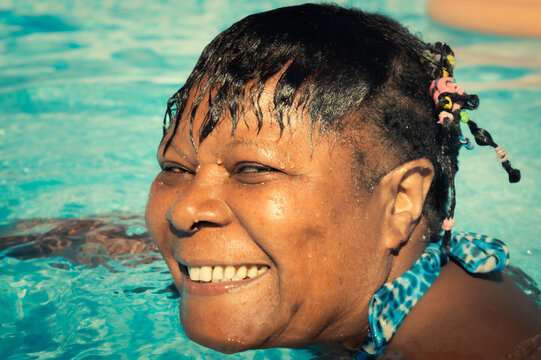 Cheerful smiling African American woman swimming in the pool on a sunny day