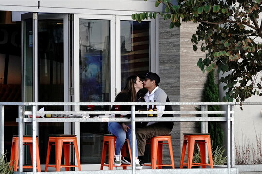 A couple dines outdoors at a restaurant in the Ocean Beach neighborhood of San Diego