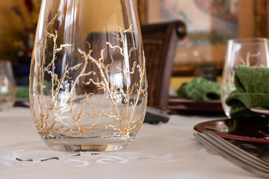 A stemless wine glass with painted gold and silver vines on its sides sits empty on a finely decorated table in anticipation of a birthday dinner. February 2021, Ontario, Canada.