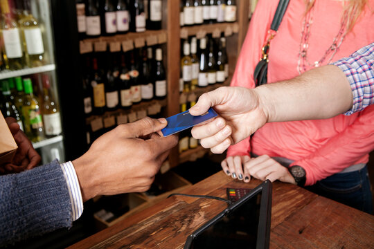 High angle view of small business owner taking credit card from customer at wine shop