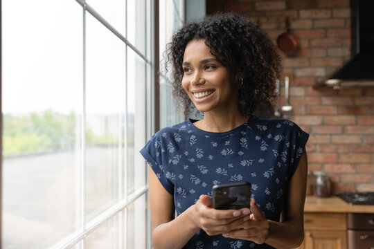Close up dreamy smiling African American woman holding smartphone, looking out window, visualizing, distracted from phone, chatting online with boyfriend or waiting for call, enjoying leisure time