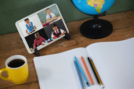School children learning on tablet screen on desk during video call
