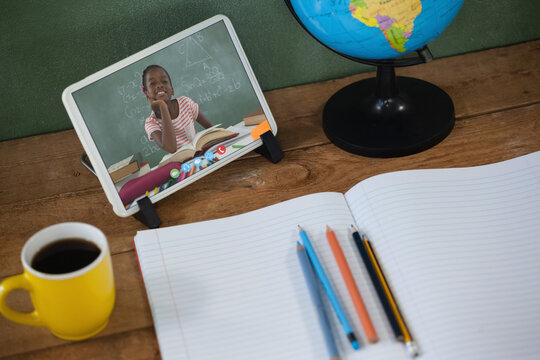 African american schoolgirl learning on tablet screen on desk during video call
