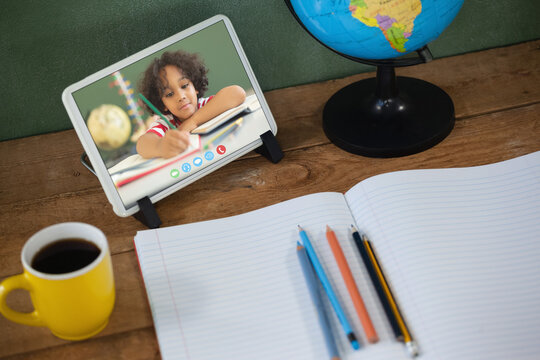 Mixed race schoolboy learning on tablet screen on desk during video call