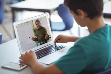 Male caucasian student having a video call with male teacher on laptop at school