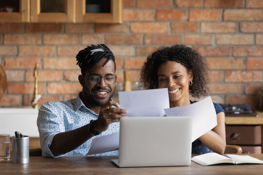 Close up happy African American family reading documents, holding papers, using laptop, wife and husband calculating domestic bills, planning budget, browsing online banking service in kitchen