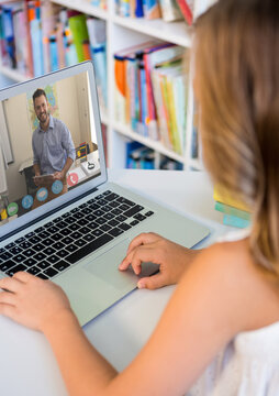 Female student having a video call with male teacher on laptop at the library