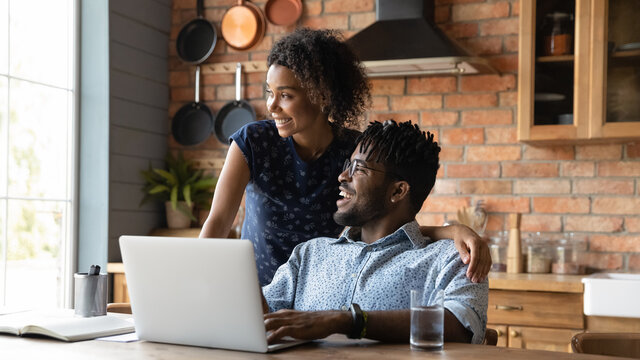 Close up happy dreamy African American couple distracted from laptop, visualizing good future, planning, looking to aside, smiling wife and husband spending leisure time in kitchen together
