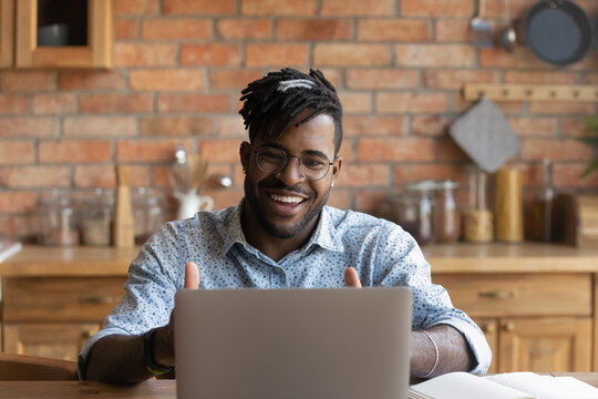 Close up smiling African American man wearing glasses using laptop, looking at screen, making video call, speaking, happy student involved in internet conference, webinar, studying at home in kitchen