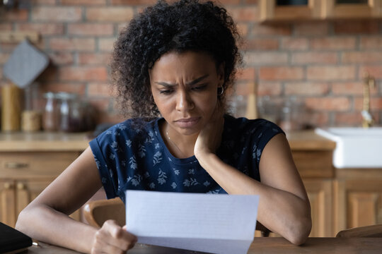 Close up unhappy African American young woman reading letter, document, frustrated businesswoman or student received bad news, unexpected debt or job dismissal notification, financial problem