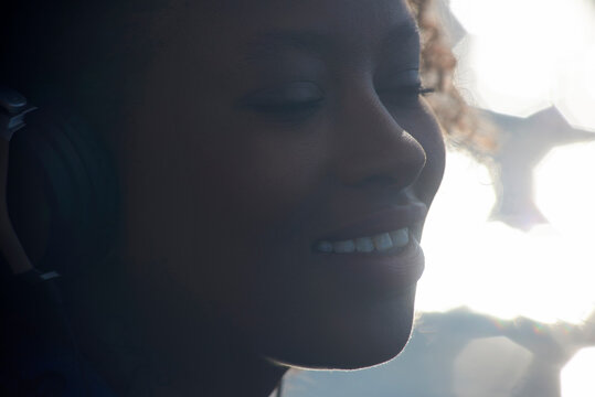 Close-up of smiling woman with eyes closed listening music