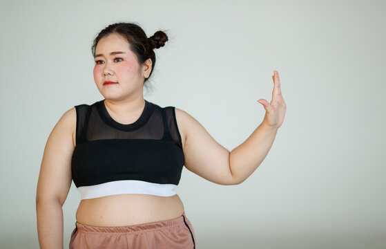 Young and lovely cute Asian fat woman in sport wear pose to camera with a happy and positive gesture with self-confidence. She rises her hand as the signal of prohibition, stops and refuses something