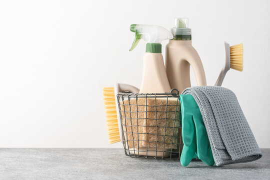 Brushes, sponges, rubber gloves and natural cleaning products in the basket.  Eco-friendly cleaning products