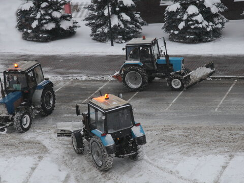 Three wheeled traktor machines cleaning a snow with scraper shovel blade on empty parking lot after heavy snowfall at winter evening, top side view on pine trees background