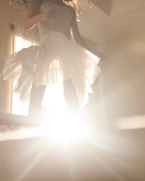 Low section of playful girl dancing on bed at home during sunny day