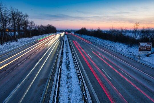 Befahrene Autobahn mit Langzeitbelichtung aufgenommen mitten in Deutschland bei Sonnenuntergang.
