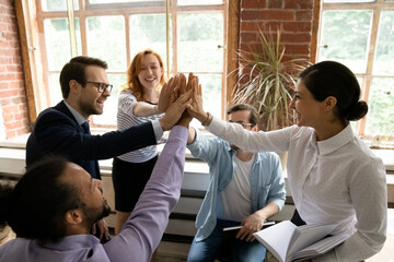 Excited diverse multiracial businesspeople give high five engaged in teambuilding activity at team office meeting. Happy multiethnic colleagues celebrate work result at briefing. Teamwork concept.