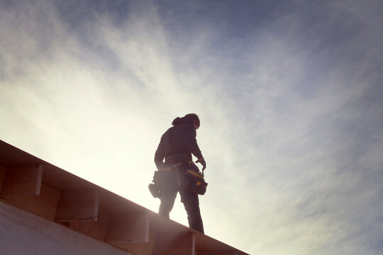 Low angle view of architecture standing on roof beam during sunny day
