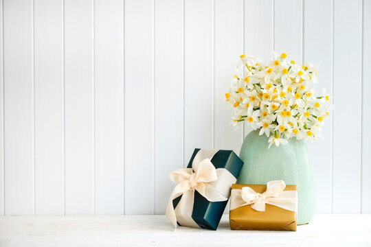 Lush bouquet of white-yellow daffodils in vintage turquoise vase and presents, wooden plank wall background. Tender minimalistic spring flowers composition. Top view, copy space, flat lay, close up.