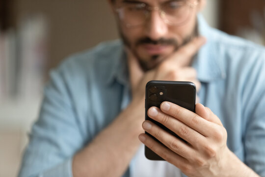 Crop close up of man hold modern smartphone gadget look at screen text or message online. Caucasian male use cellphone browse surf wireless internet on device. Communication, technology concept.