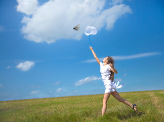 girl with a ring-net on a summer filed. Sunny day. smiling girl holds butterfly net on blue sky with clouds. young adult  woman catching a butterfly in scoop-net. Female with long hair. Wall mural