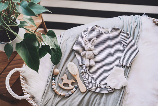 Still life background of cute baby products - changing basket with baby bodysuit, newborn clothes, knitted rabbit and wooden toy. Minimalist style photography of baby shower, pregnancy announcement.