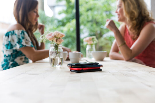 Female friends having coffee together at cafe with smart phones on table