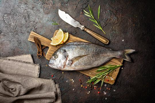 Fresh fish dorada or gilt-head bream on cutting board with spices, lemon and knife