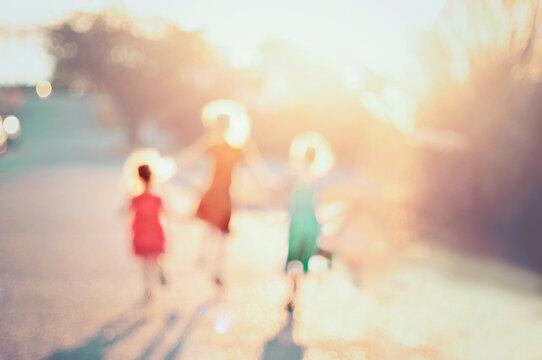 Defocused image of girls playing on street during summer