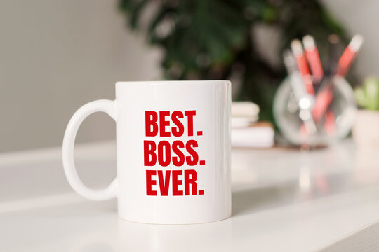 Coffee mug with text BEST. BOSS. EYER. in workplace background.
