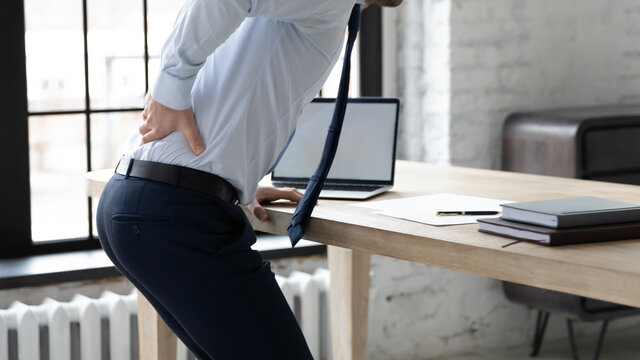 Close up of unhealthy male employee stand from desk sit in incorrect posture suffer from muscular strain or spasm. Unwell man worker struggle from backache or pain in office. Sedentary life concept.