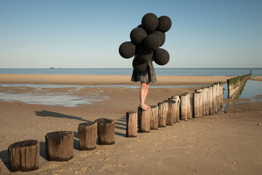 Girl in black dress holding bunch of black balloons on the beach