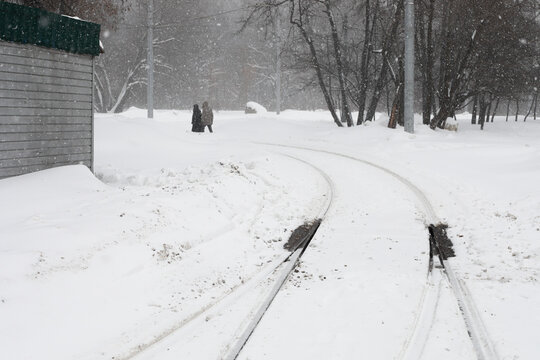 Moscow, Russia. 13th February 2021. A blizzard covered the city. Two people far are walking following the tram tracks under the snow.
