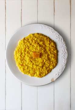 Risotto alla Milanese dressed with saffron threads and a Parmigiano Reggiano cheese rind on a white wooden table. Italian cuisine.