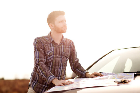 Man with map looking away while standing by car against clear sky