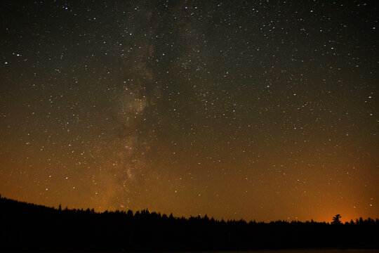 Scenic view of star field over silhouette landscape at night