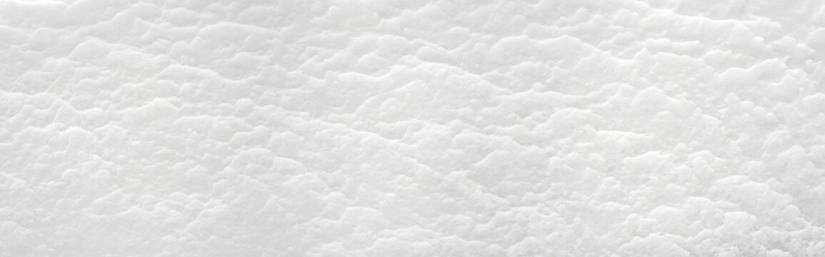 Snow texture background..A snowdrift of many snow layers. .A deposit of snow sculpted by the wind..Еmbossed snow surface..Winter concept..White background. Close up..Panoramic image. Hi-res banner.