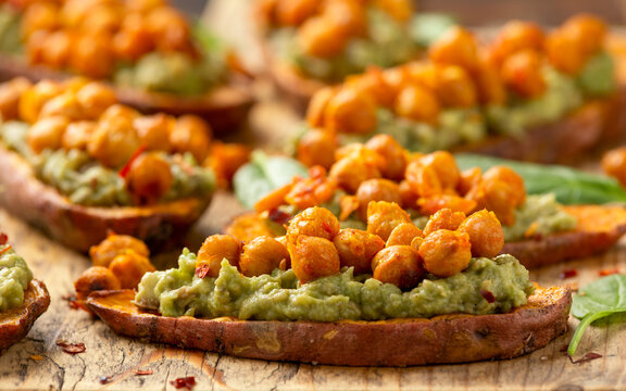 Sweet potato toast loaded with avocado guacamole and baked chickpeas sprinkled with chili flakes served on wooden board