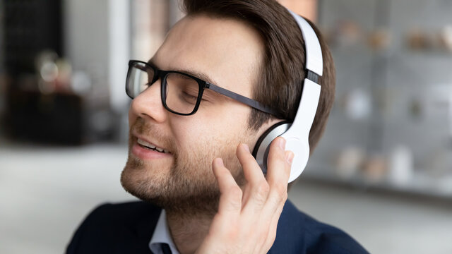 Close up of calm happy young Caucasian businessman wear headphones enjoy good quality sound on gadget. Smiling male boss or CEO relax rest listen to music in earphones in office. Technology concept.