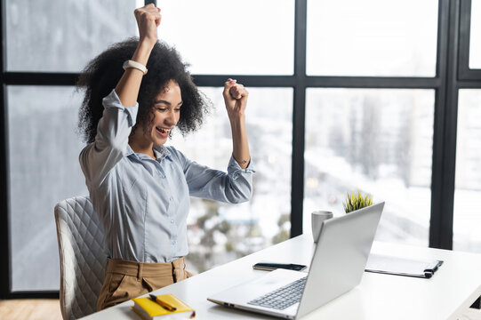 African-American woman with curly hairstyle hands up,at the desk with open laptop,wide smile,excited by the news,celebrating her success,accepted for internship,admitted to university, got a letter