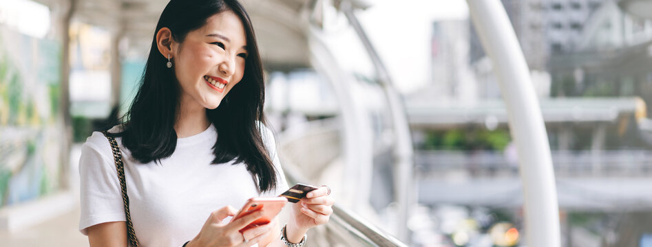 Young adult business asian woman consumer using creadit card and smartphone for shopping online.
