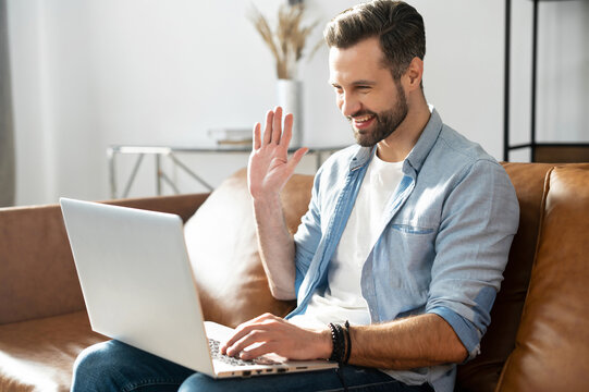 Glad and smiling young bearded hipster talking via video call on the laptop at home, handsome guy sits on the cozy sofa and waving hello into webcam, video meeting, remotely conference from home
